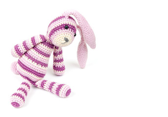 Knitted rabbit toy sits isolated on white