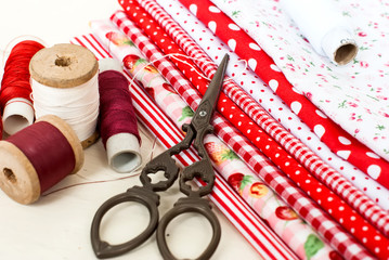 colored fabric spools of thread and scissors for sewing