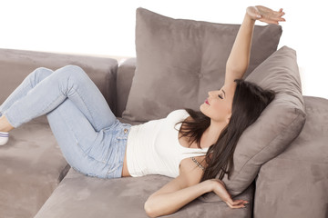 a beautiful young woman lying on the couch and stretching