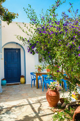 Entry to typical Greek house with blue dores and green trees in