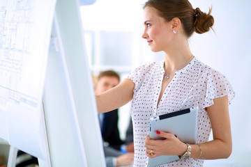 Businesswoman writing on flipchart while giving presentation to