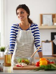 Young woman mixing fresh salad