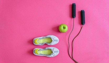 Sport shoes, apple and rope on pink sport mat. Top view angle