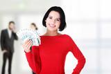 Young woman holding polish bills.