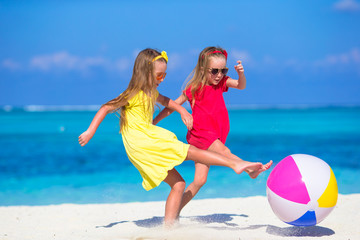 Little adorable girls playing on beach with air ball