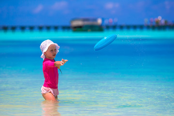 Little girl playing with flying disc at white beach