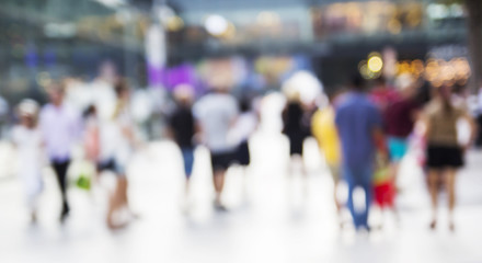 Abstract people are walking in the city. Blurred background.