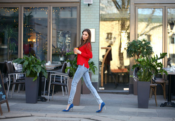 Young beautiful girl in jeans and a red blouse is walking down t