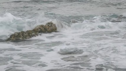 Waves wash over an exposed rock as they head to shore.