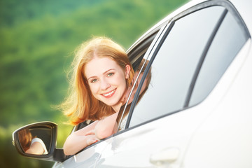 happy woman looks out the car window on nature