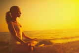 Fototapety woman meditating in lotus pose on the beach at sunset