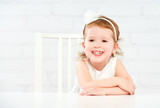 Happy fun funny girl child laughing at  empty white table