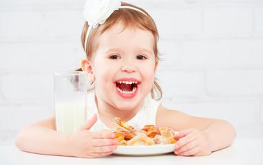 happy child  girl eats cookies and milk