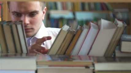 boy chooses a book in the library. close up. slow motion