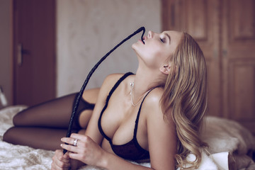 Sexy blonde woman in underwear bite whip