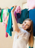 Happy housewife drying clothes