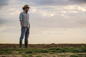 Male Farmer Standing on Fertile Agricultural Farm Land Soil
