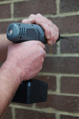 Man using a battery operated hand drill