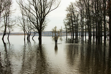 Man standing in the water in flooded field