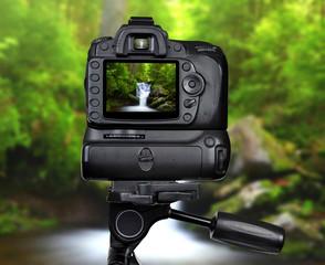 Dslr camera on tripod photographing waterfall