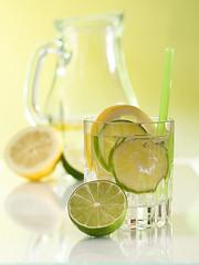 Mineralwasser mit Limetten-, Zitronenscheiben und Eiswürfeln