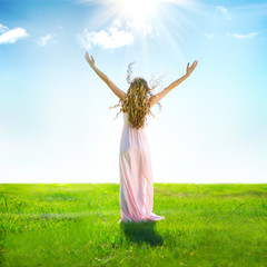 Beautiful woman outdoor raising hands in sunlight rays