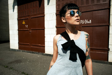 black haired tattooed lady wears sunglasses in backyard