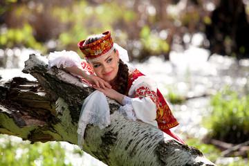 Beautiful girl in a russian national dress outdoors
