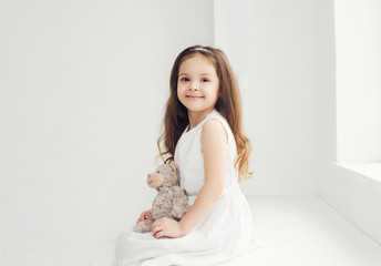 Beautiful little girl with teddy bear in white room