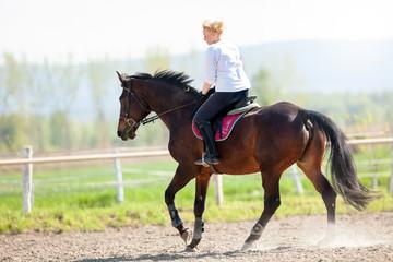 Beautiful blonde woman riding a horse