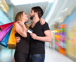 Happy couple with shopping bags . Man holding credit card