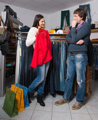 Woman shop assistant showing shirt to man