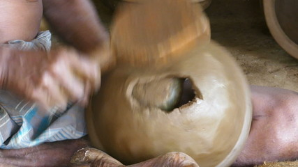 hands of a potter manufactured a pot of clay