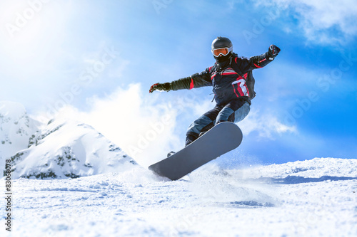 Poster Jumping snowboarder from hill in winter