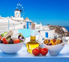 Greek salad against windmill in Santorini island, Greece