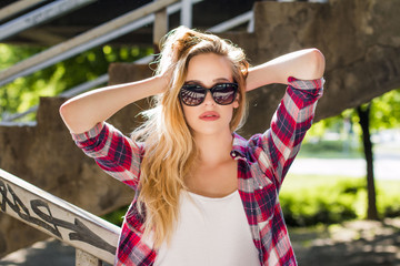 Trendy Hipster Girl with Sunglasses standing on the stairs