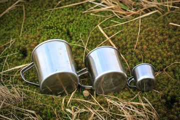 Group of three steel cups on grass