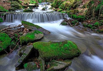 green stones in water of mountain stream
