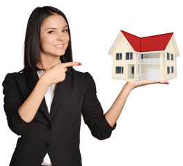 Woman standing and holding hand country house on pointing at it