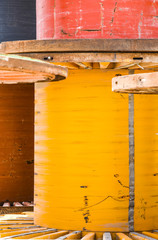 Yellow used cable spool standing on its end