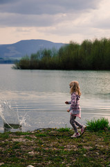 girl throwing stones into pond