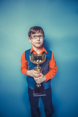 European-looking  boy of ten years in glasses holding a cup, awa