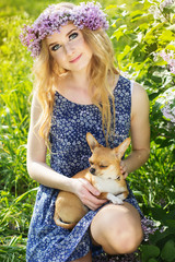 Beautiful girl with a wreath of lilac flowers and dog