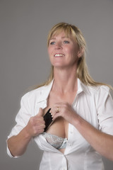 Woman putting mobile phone into her bra for safe keeping