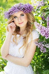 Portrait of beautiful girl with wreath from lilac flowers