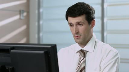 Surprised clerk. Manager works on a computer.