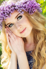 Portrait of beautiful teen girl with wreath from lilac flowers