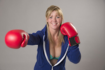 Woman wearing red boxing gloves ready to fight