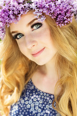 Blue-eyed girl with wreath from lilac flowers