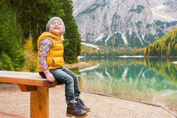 Blonde young girl sitting on picnic table at Lake Bries